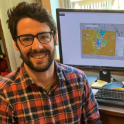 A picture of Austin L. Holland smiling at the camera from his desk and wearing a plaid flannel shirt.