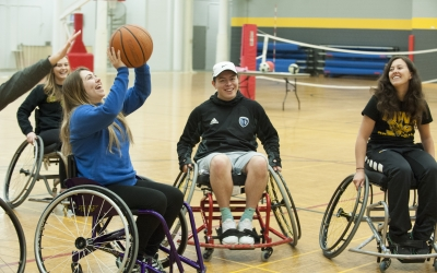 Students using wheelchairs play basketball during Hoopfest.