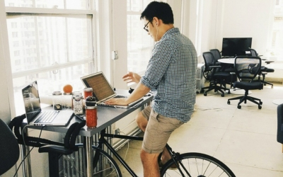 Man uses stationary bike while working at his desk.