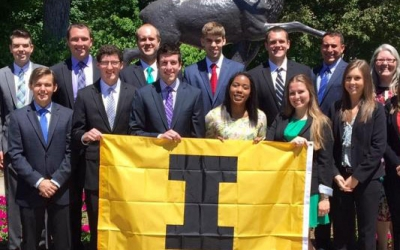 Sport and recreation management students pose with University of Iowa flag.