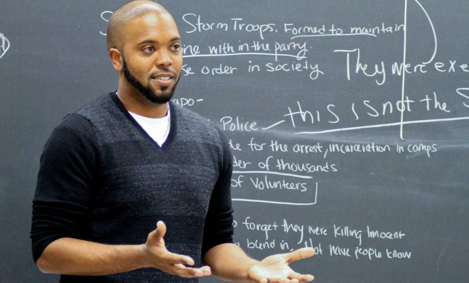 A graduate student in front of a chalkboard