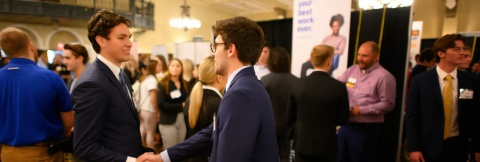 students shaking hands at event