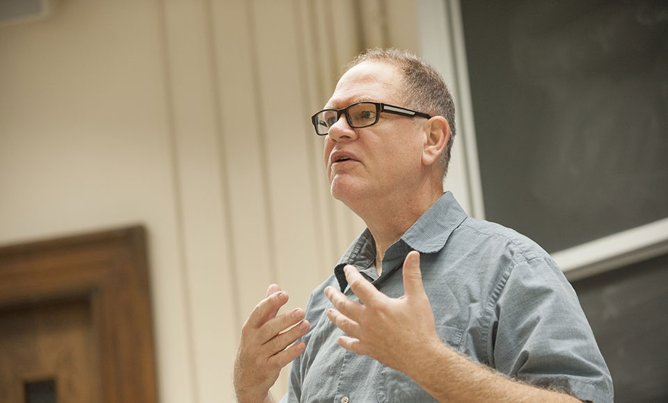 A a Religious Studies professor gives a lecture to his class.