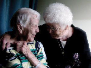 An elderly couple embracing each other