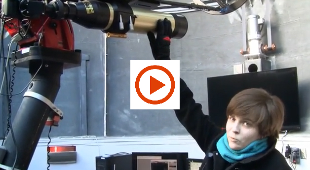ERin Maier with telescope and play button for video