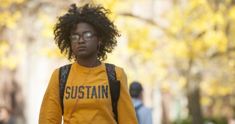 Iowa student walking on campus surrounded by golden autumn leaves