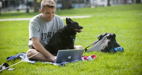 student with his dog studying on pentacrest lawn