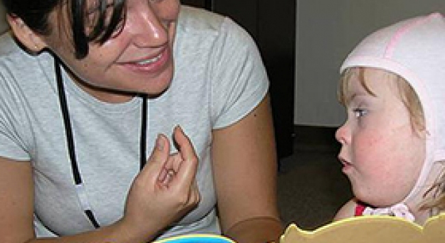 UI student with small child in speech and hearing clinic